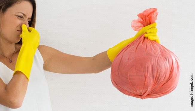 A woman holding a bag full of trash