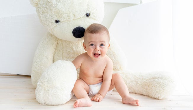 a baby boy in a diaper sitting next to a giant teddy bear